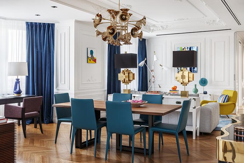 duży drewniany stół zniebieskimi fotelami pod żyrandolem zkloszami wkształcie instrumentu dętego