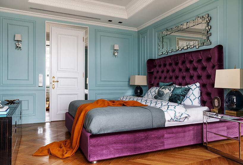 elegancka niebieska sypialnia zdużym fioletowym łóżkiem zwysokim oparciem pod wyjątkowym lustrem