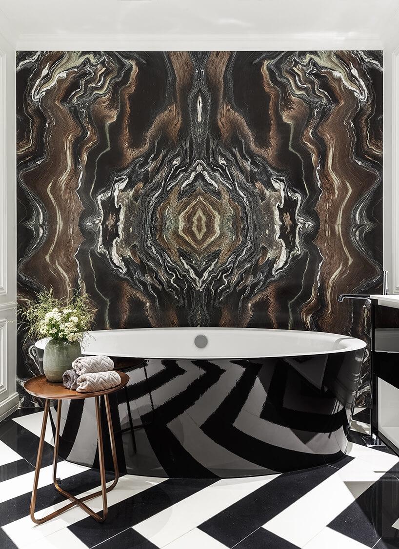 elegancka łazienka zbiało czarną podłogą zdużą wanną zabudowaną błyszczącym czarnym materiałem na tle ściany znaturalnego ciemnego kamienia