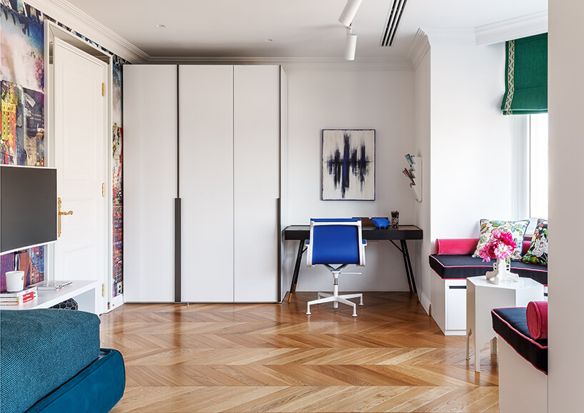 biały pokój dla dzieci zdrewnianym parkietem zbiałą szafą zczarnymi wstawkami obok czarnego biurka zbiało niebieskim krzesłem