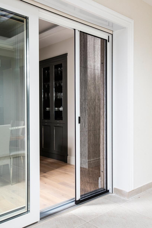 białe przysuwane drzwi tarasowe zbrązowymi moskitierami ANWIS
