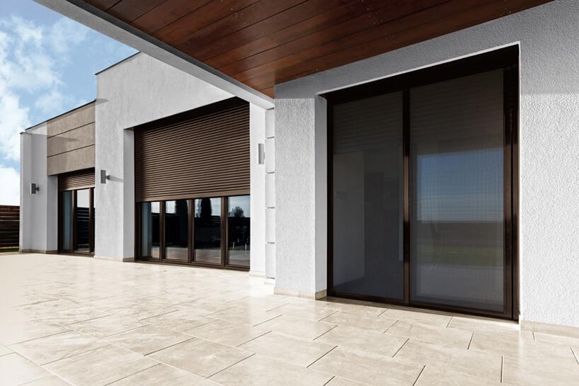 brązowe trzwi tarasowe wbiałej elewacji budynku zbrązowymi moskitierami ANWIS