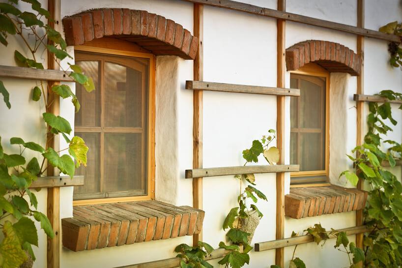 dwa okna wstarym budynki zceglanym parapetem izmoskitierami ANWIS