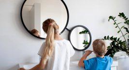 dwoje dzieci przy białej szafce łazienkowej podczas mycia zębów