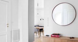 duże lustro nad drewnianą komodą wprzestronnym białym wnętrzu