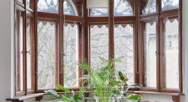 wyjątkowe dwa fotele wwersji szarej idrewnianej wna tle okien wsalonie