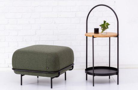 ciemno-zielona pufa obok stolika na tle białej ściany