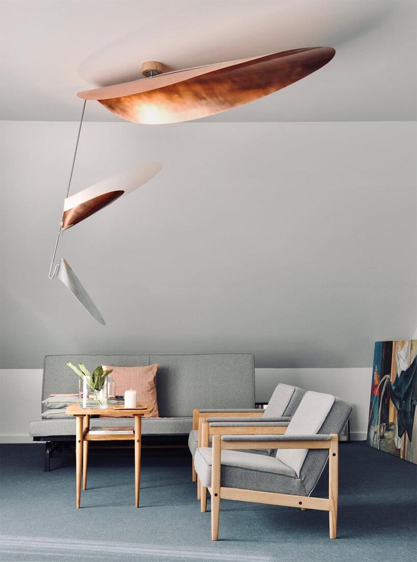 szare wnętrze zsofą idwoma krzesłami pod lampami Wspólna/Wspólny