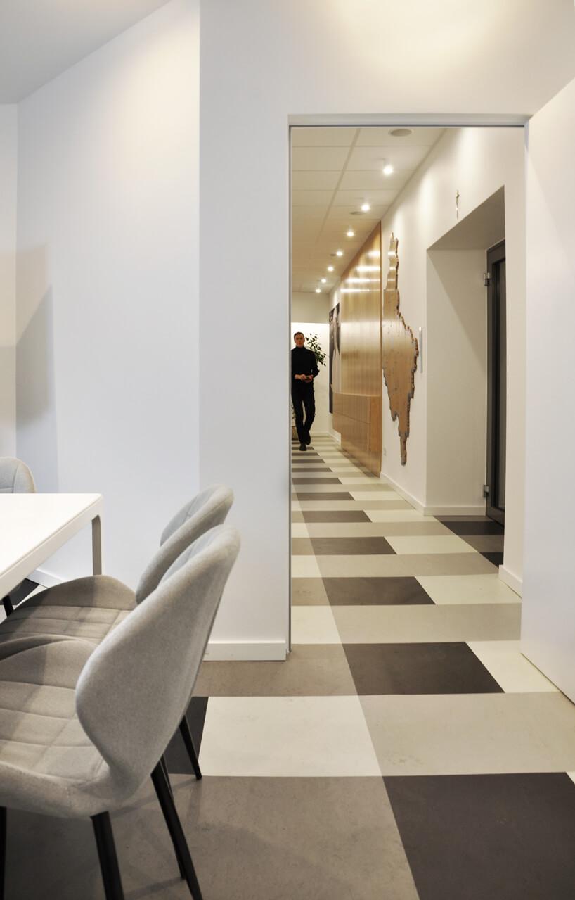wnętrze biurowe zbiałymi ścianami ikraciasta podłogą oraz drewnianymi akcentami na ścianie