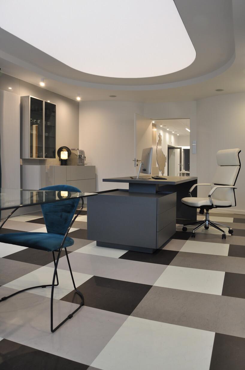 szare wnętrze biura zdużym nowoczesnym biurkiem ibiałym fotelem