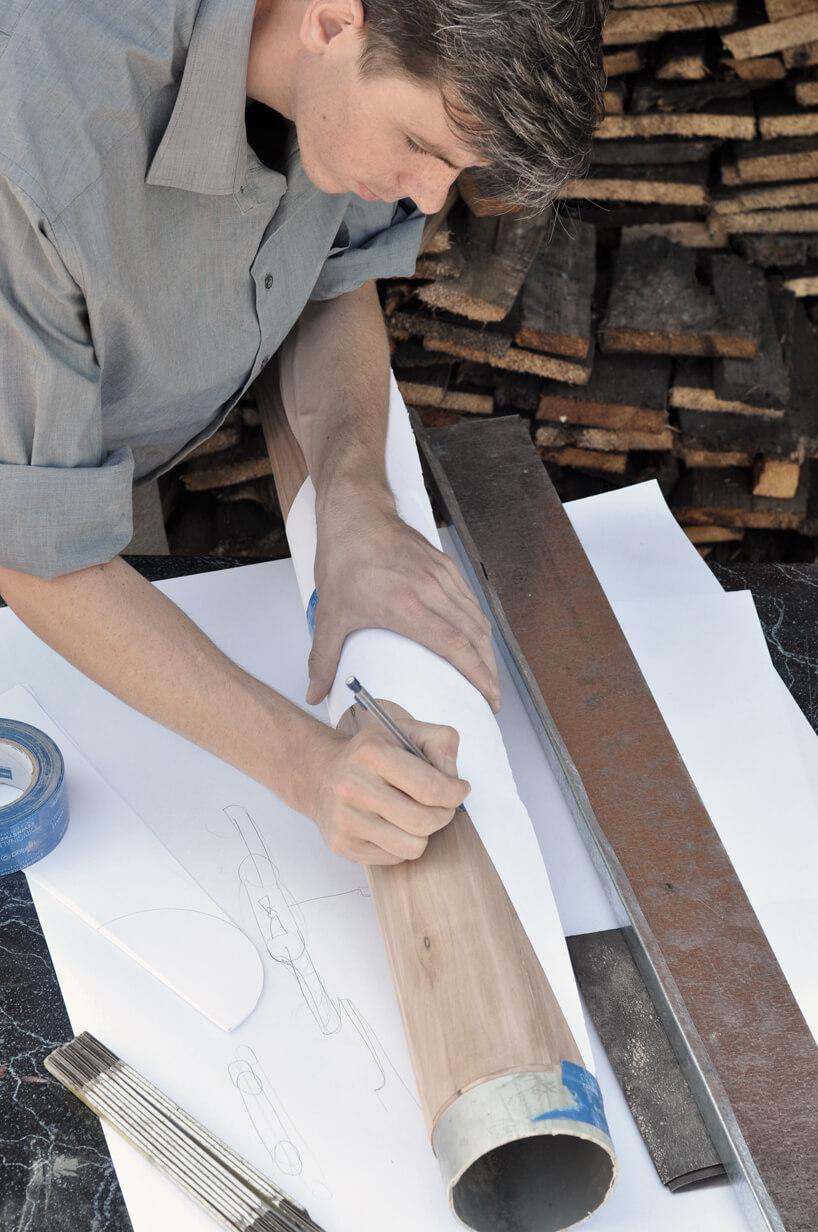 mężczyzna podczas nanoszenia na drewno projekktu