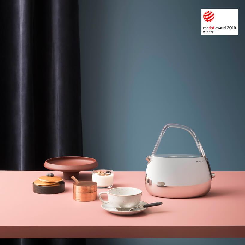chromowany czajnik na różowym blacie obok zestawu kawowego