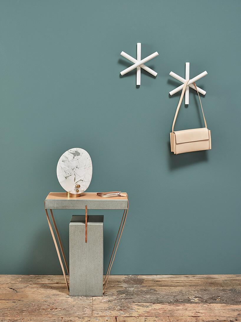 drewniany wieszak wkształcie gwiazdy od ton na ścianie wkolorze butelkowej zieleni