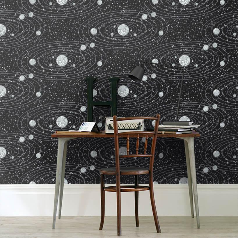 czarna tapeta Orbit jako tło dla małego stolika zmaszyna do pisania