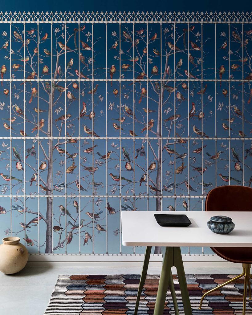 niebieska tapeta Uccelli zdrzewami iptakami za ogrodzeniem