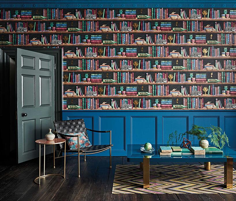 salon zmałym stolikiem iczarnym fotelem ztapetą zmotywem biblioteki