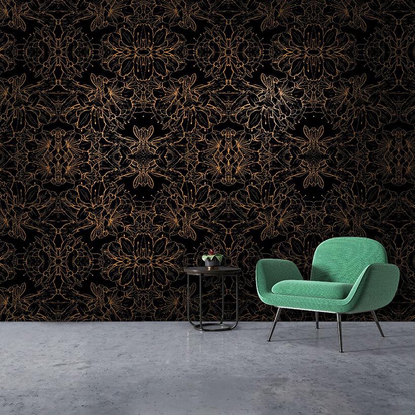 elegancka czarno złota tapeta Les Fleurs jako tło dla zielonego fotela imałego czarnego stolika