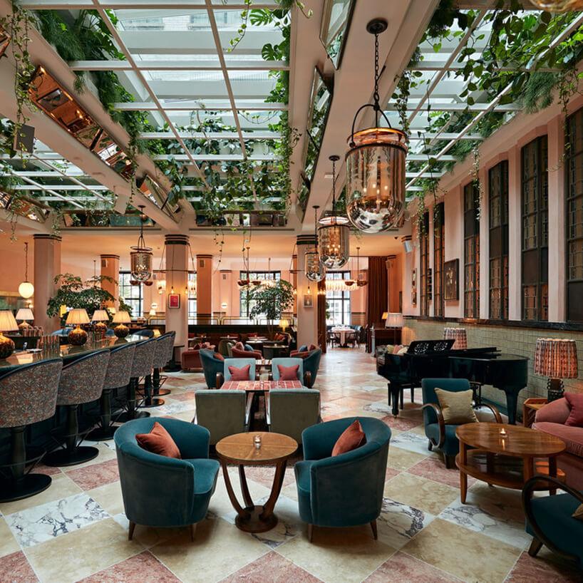wnętrze restauracji Soho House zprzeszklonym sufitem izwisającym roślinami
