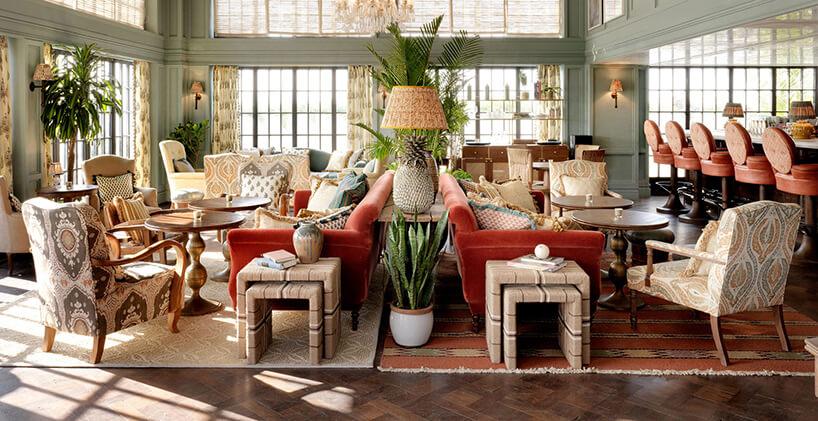 wnętrze restauracji zklasycznymi domowymi fotelami na dywanach na ciemnej drewnianej podłodze