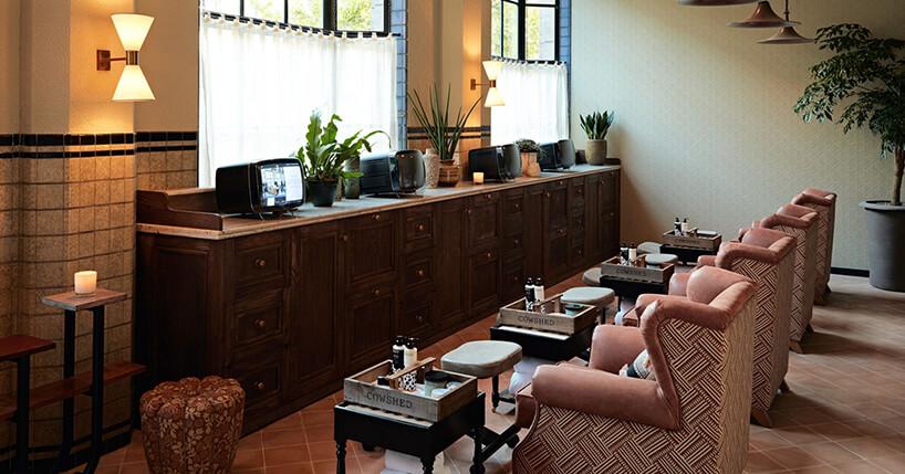 wyjątkowy salon urody zfotelami przed brązową komodą zmałymi telewizorami
