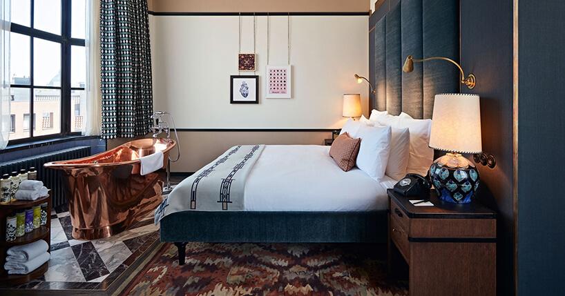 miedziana wanna wsypialni zdużym niebieskim łóżkiem