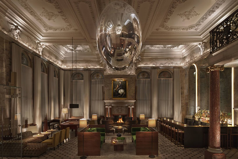 ciemna elegancka przestrzeń restauracyjna pod zdobionym sufitem zduża błuszcząca kulą