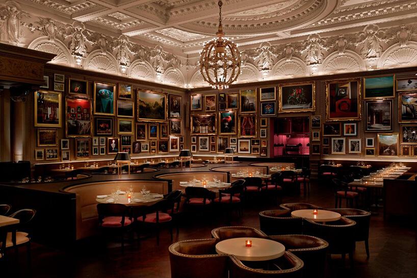 eleganckie ciemne wnętrze restauracji ze ścianami pełnymi obrazów