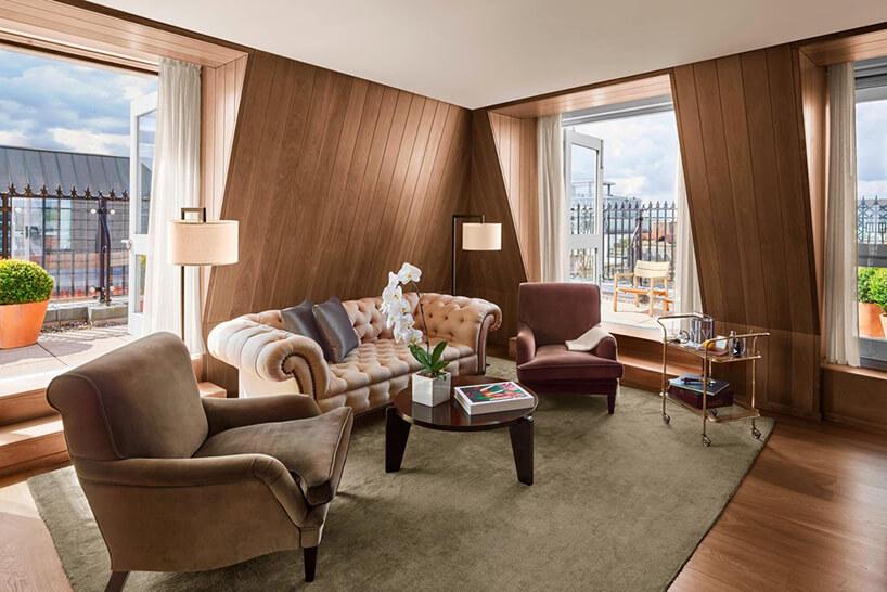 elegancki san ze skośnym drewnianymi ścianami zbeżową sofą zdwoma fotelami