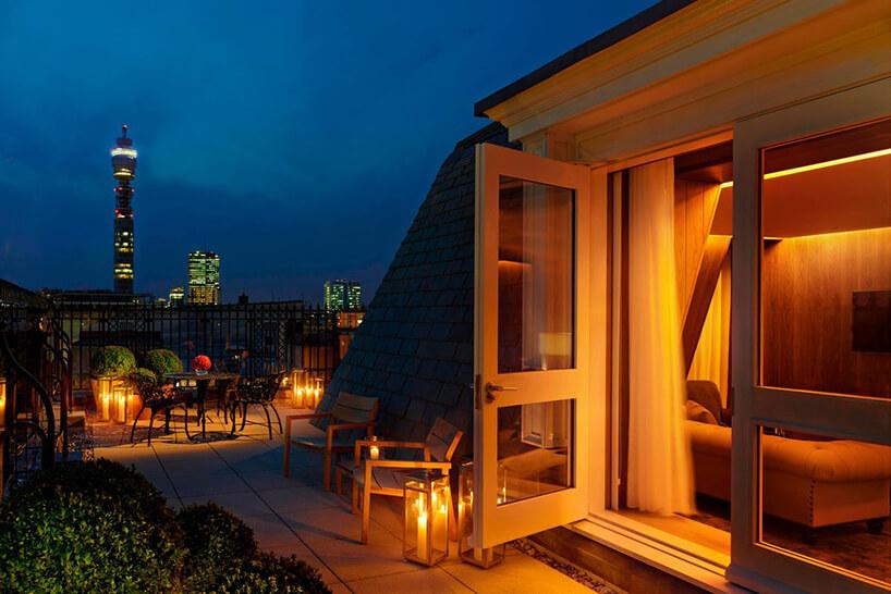 taras nocą doświetlony świecami na tle wysokiego budynku