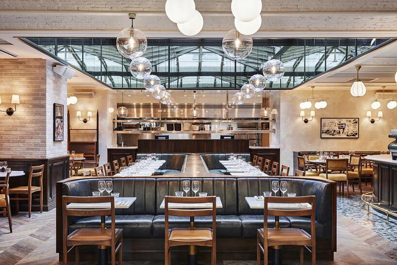 eleganckie wnętrze restauracji ze skórzanymi sofami zmałymi stolikami zdrewnianymi krzesłami