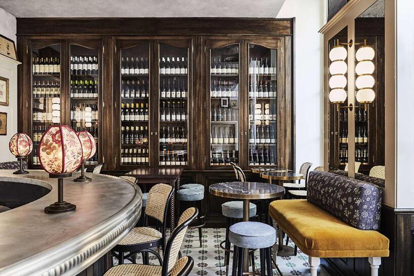 elegancki bar owalny na tle wysokie ciemno brązowej szafy pełnej win