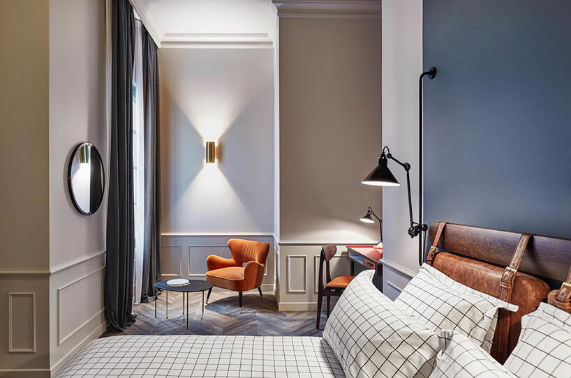 elegancka jasna sypialnia zdużym łóżkiem na tle pomarańczowego fotela
