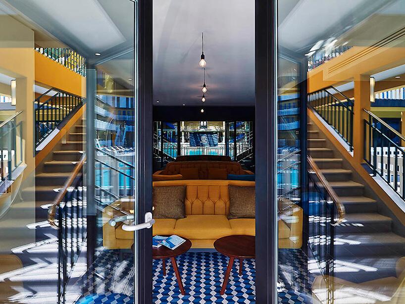 duża żółta sofa zdwoma brązowymi stolikami za lekko otwartymi szklanymi drzwiami