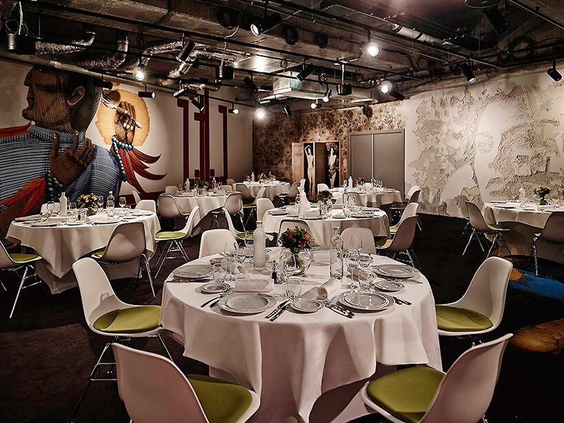 nowoczesna przestrzeń restauracyjna zdużym stolikami iróżnymi wizerunkami na ścianach