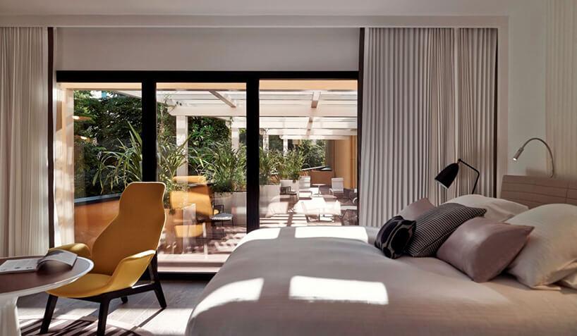 nowoczesna sypialnia zjasnym łóżkiem obok żółtego fotela na tle przeszklonych drzwi na taras