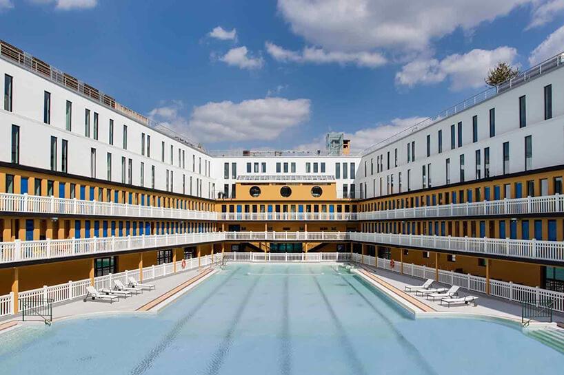 biało żółty hotel zbiałym balustradami wokół basenu