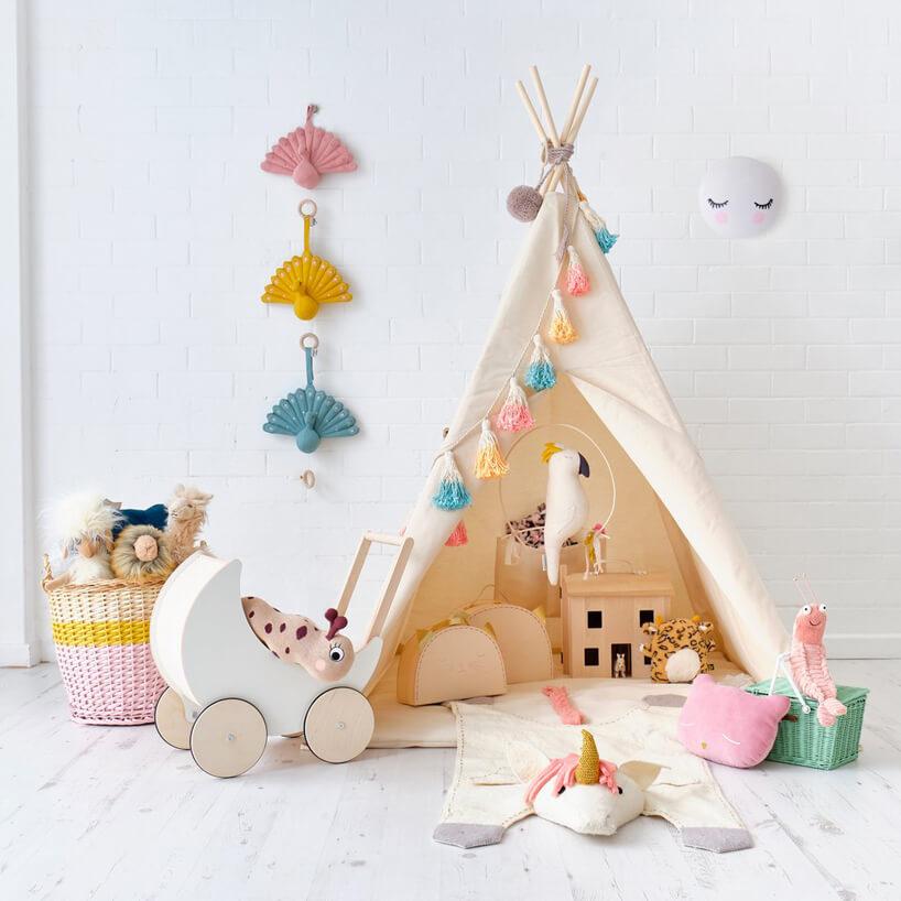 beżowy namiot indiański dla dziecka biały mały wózek dla dziecka na tle szarej ściany