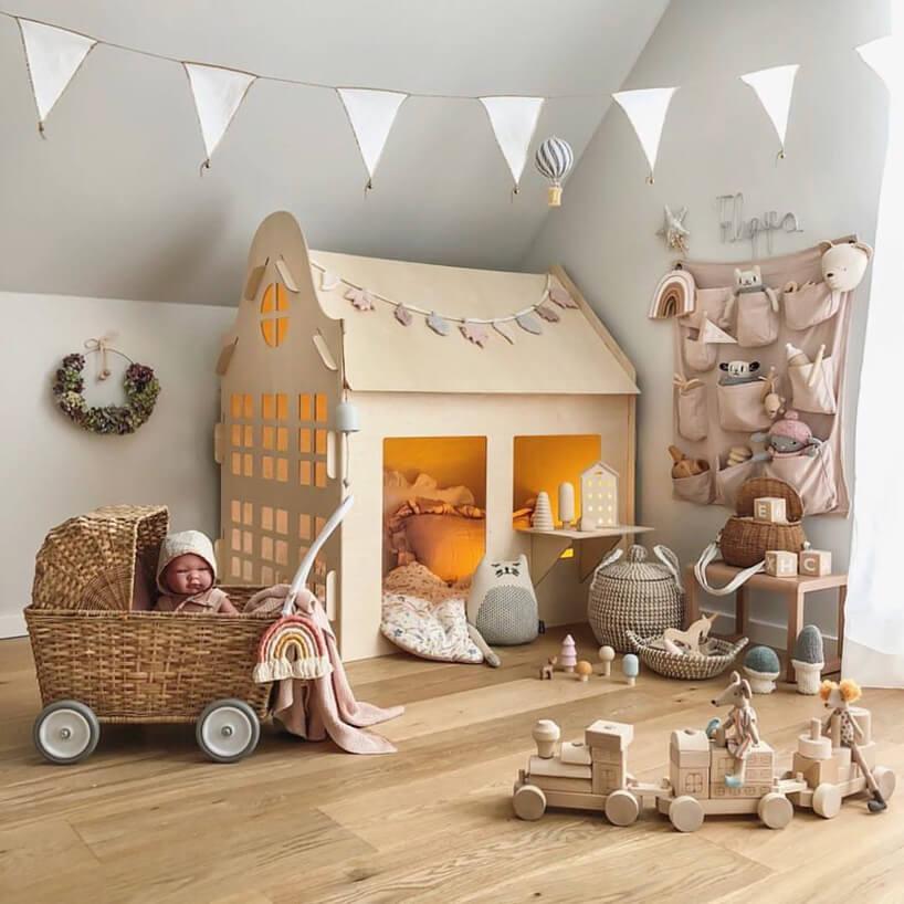 pomarańczowy domek dla dziecka wózek dla lalek drewniany pociąg na tle białej ściany