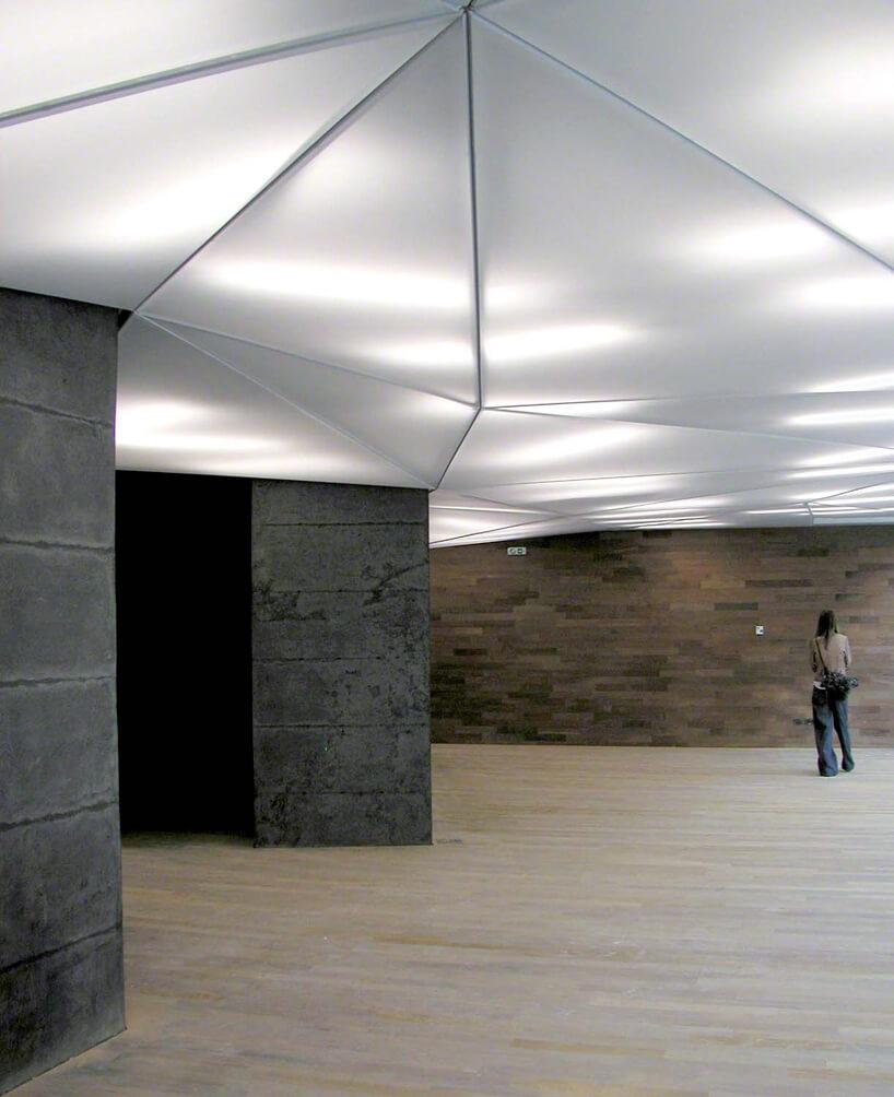 biały napinany sufit we wnętrzu wyłożonym kamieniem