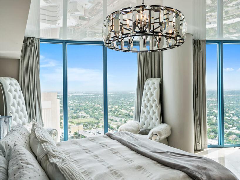 elegancka sypialnia zwidokiem zwysokiego piętra ibłyszczącym napinanym sufitem