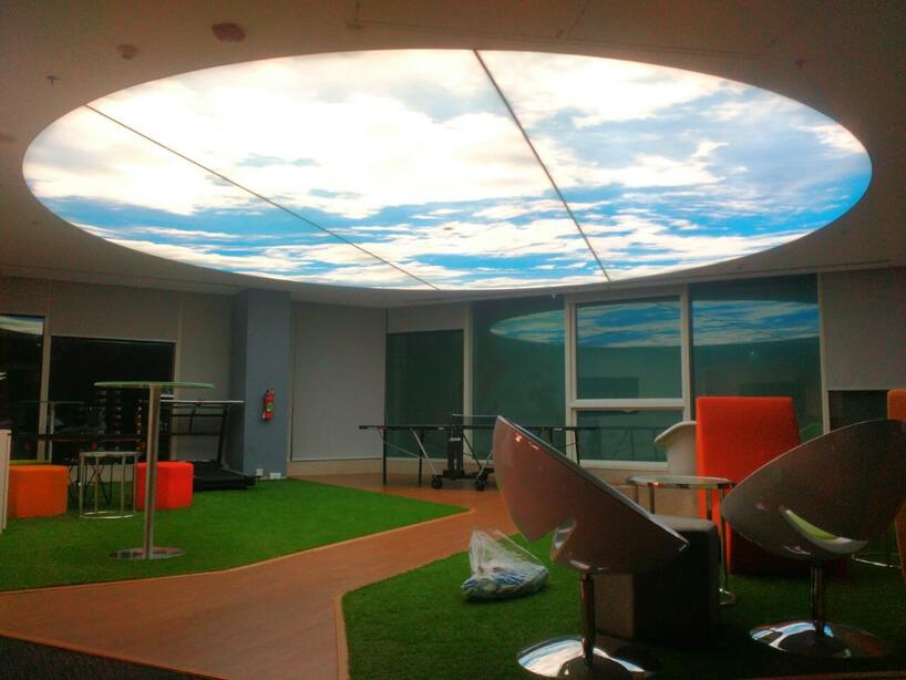 open space ze świetlikiem przysłoniętym przez napinany sufit zgrafiką nieba zchmurami