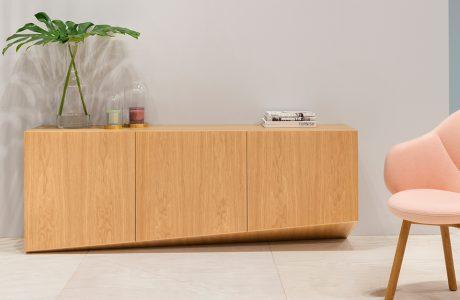 nowoczesna komoda w kolorze jasnego drewna obok różowego fotela
