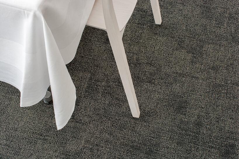 białe krzesło zstolikiem iobrusem na szarej wykładzinie