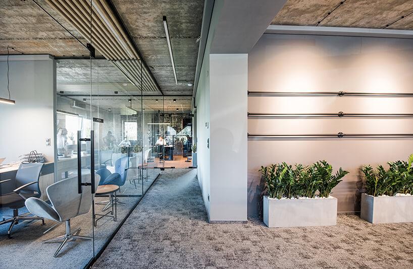 przestrzeń biurowa ze szklaną ścianą oraz białymi donicami zroślinami