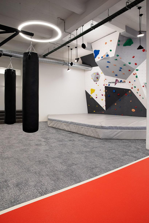 szaro-czerwona wykładzina przy czarnych workach treningowych oraz małej ściance wspinaczkowej