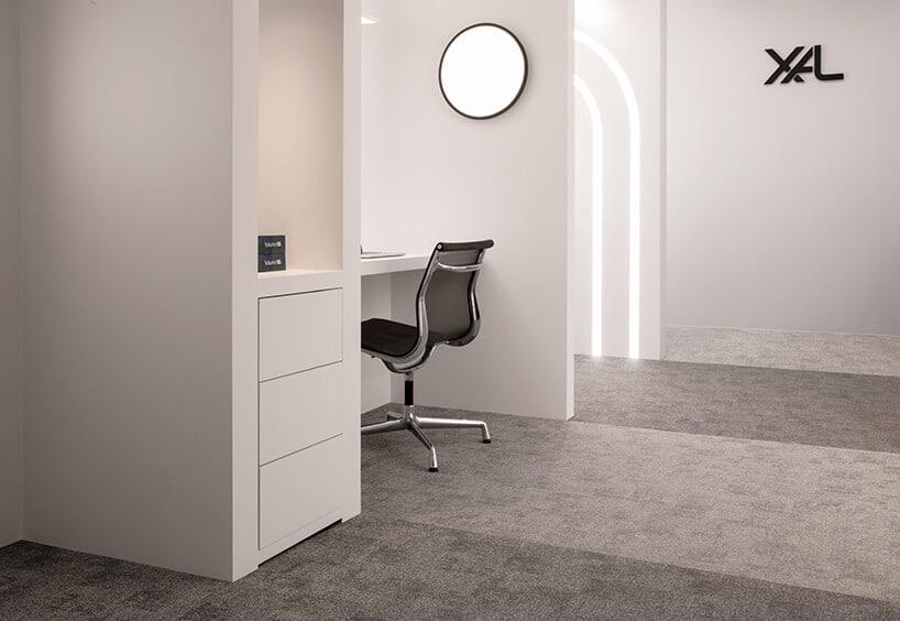 przestrzeń do pracy zczarnym krzesłem obok białej szafy