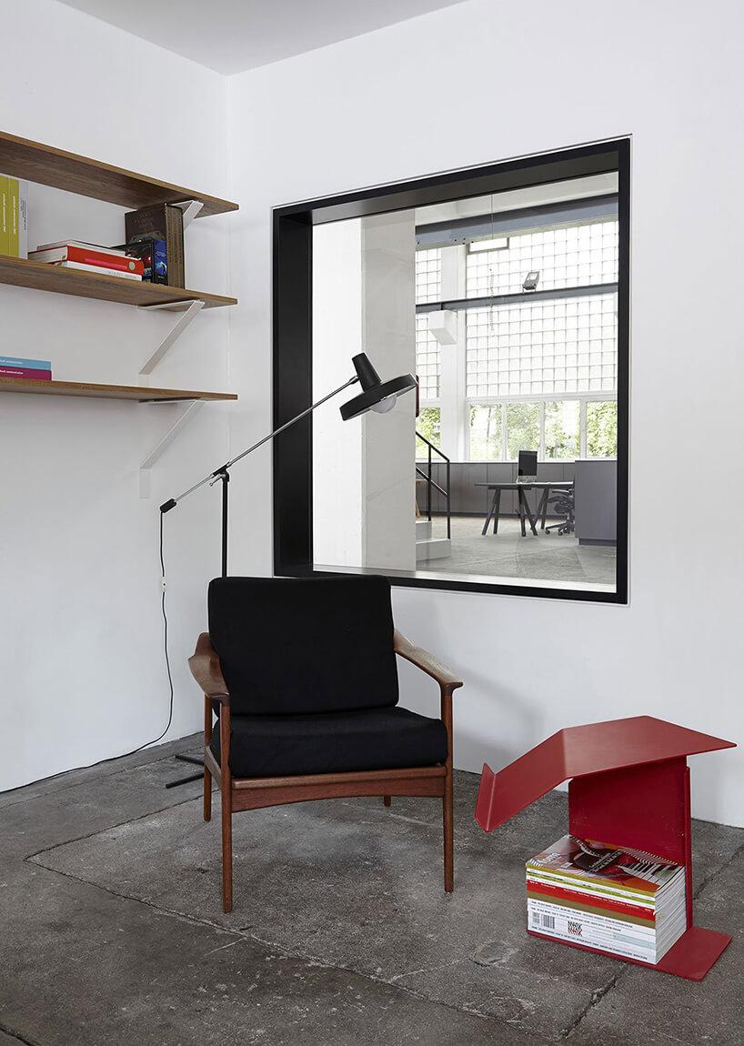 czarny fotel zczerwonym stolikiem ilampka