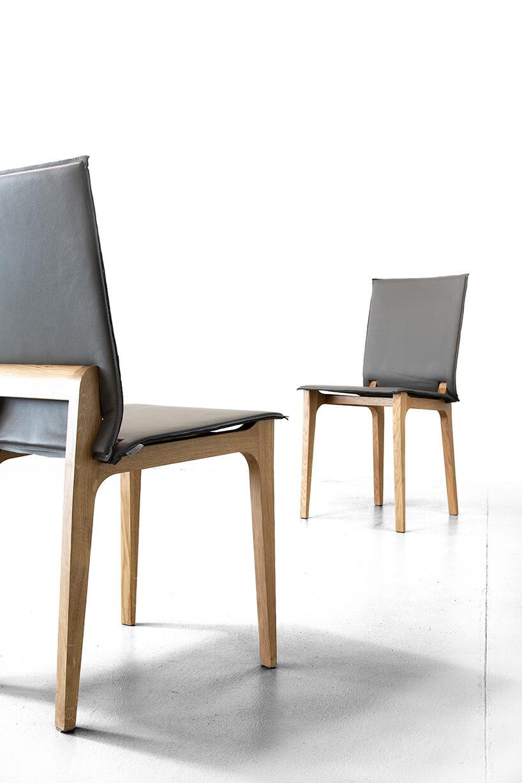 dwa nowoczesne drewniane krzesła zszarym skórzanym siedziskiem ioparciem