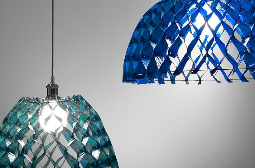 dwie nowoczesne lampy Kalky od Bozzetti zzielonym iniebieskim kloszem zpołączonych obszytych plastikowych pasków