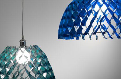 dwie nowoczesne lampy Kalky od Bozzetti z zielonym i niebieskim kloszem z połączonych obszytych plastikowych pasków
